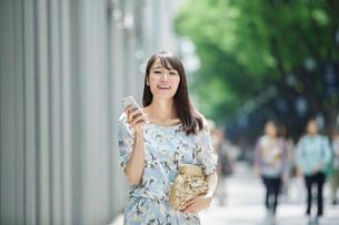 スマートフォンを持ち街を歩く女性の写真素材 [FYI01801573]