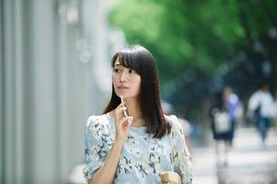 スマートフォンを持ち街を歩く女性の写真素材 [FYI01801601]