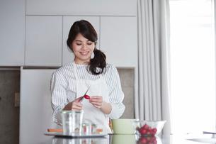 キッチンに立ち料理を作る女性の写真素材 [FYI01801608]