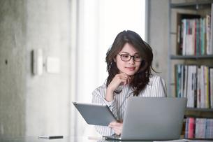 オフィスでノートパソコンを開き仕事をする女性の写真素材 [FYI01801610]