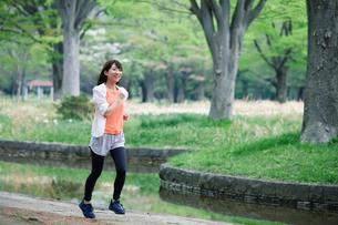 緑の中を走る女性の写真素材 [FYI01801620]