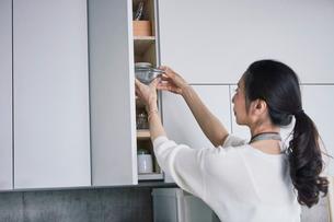 食器棚と女性の写真素材 [FYI01801635]