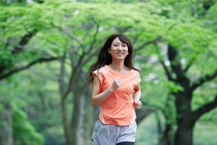 緑の中を走る女性の写真素材 [FYI01801670]