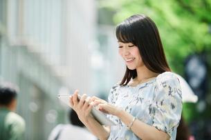街でタブレットPCを持つ女性の写真素材 [FYI01801677]