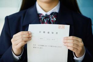 合格通知書を持ち微笑む女子学生の写真素材 [FYI01801706]