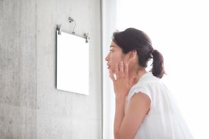 鏡の前でスキンケアをする女性の写真素材 [FYI01801707]