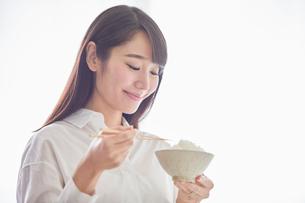 お茶碗に入った白米を食べる笑顔の女性の写真素材 [FYI01801708]