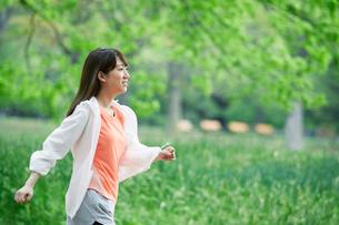 緑の中を走る女性の写真素材 [FYI01801714]