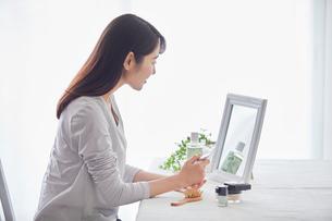 鏡の前でスキンケアをする女性の写真素材 [FYI01801720]