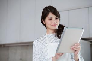 キッチンに立ちタブレットPCを持つ女性の写真素材 [FYI01801722]