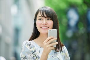 スマートフォンを持ち街を歩く女性の写真素材 [FYI01801732]