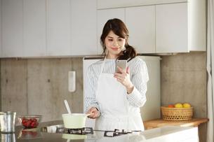 キッチンに立ちスマートフォンを持つ女性の写真素材 [FYI01801738]