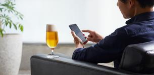 ビールを飲みながらスマホを操作する男性の写真素材 [FYI01801761]