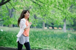 緑の中を走る女性の写真素材 [FYI01801777]