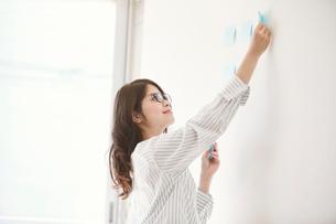 壁にふせんを貼る女性の写真素材 [FYI01801781]