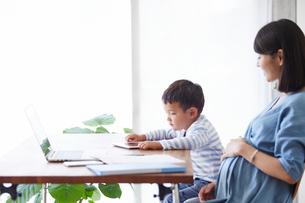 仕事をする女性とタブレット端末を見る男の子の写真素材 [FYI01801799]