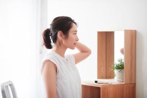 鏡の前でスキンケアをする女性の写真素材 [FYI01801801]