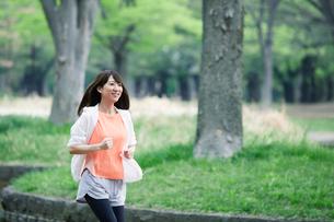 緑の中を走る女性の写真素材 [FYI01801806]