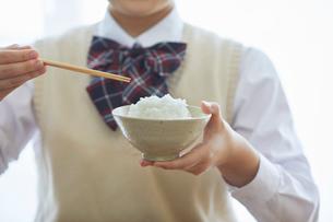 お茶碗を持ちごはんを食べる女子学生の写真素材 [FYI01801815]
