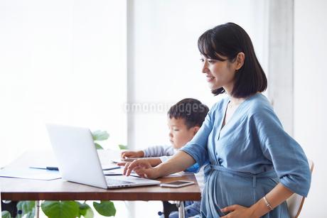 仕事をする女性とタブレット端末を見る男の子の写真素材 [FYI01801818]