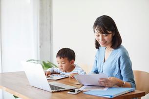仕事をする女性とタブレット端末を見る男の子の写真素材 [FYI01801822]