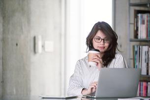 オフィスでノートパソコンを開き仕事をする女性の写真素材 [FYI01801857]