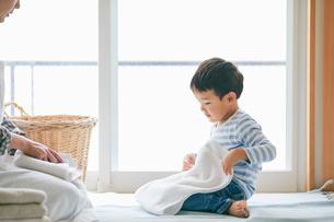 洗濯物をたたむ男の子と女性の写真素材 [FYI01801859]