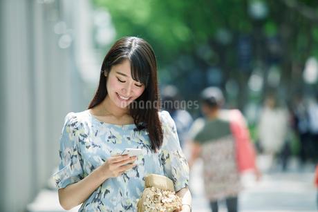 スマートフォンを持ち街を歩く女性の写真素材 [FYI01801862]