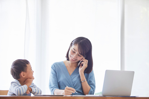 仕事をする女性とタブレット端末を見る男の子の写真素材 [FYI01801868]