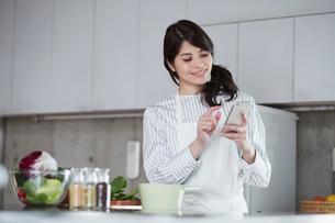 キッチンに立ちスマートフォンを持つ女性の写真素材 [FYI01801883]