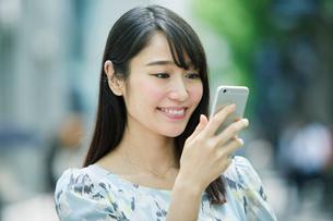 スマートフォンを持ち街を歩く女性の写真素材 [FYI01801886]