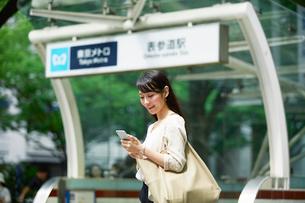 駅の前に立つ女性の写真素材 [FYI01801887]