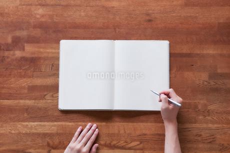 白いノートと女性の手の写真素材 [FYI01801920]