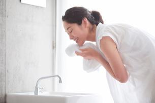 洗面所で顔を洗う女性の写真素材 [FYI01801946]