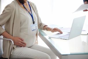 仕事をする妊婦女性と男性の写真素材 [FYI01802016]