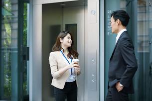 オフィスビルの前で話すビジネスマンとビジネスウーマンの写真素材 [FYI01802030]