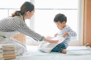洗濯物をたたむ男の子と女性の写真素材 [FYI01802031]