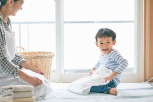 洗濯物をたたむ男の子と女性の写真素材 [FYI01802034]