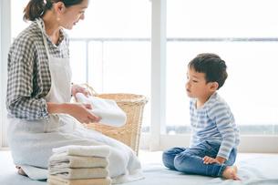 洗濯物をたたむ男の子と女性の写真素材 [FYI01802035]
