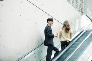 会話しながらエスカレーターに乗るビジネスマンとビジネスウーマンの写真素材 [FYI01802036]