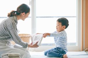 洗濯物をたたむ男の子と女性の写真素材 [FYI01802046]