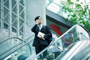 タブレットPCを持ちエスカレーターに乗るビジネスマンの写真素材 [FYI01802054]