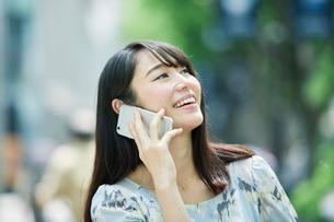 スマートフォンを持ち街を歩く女性の写真素材 [FYI01802057]