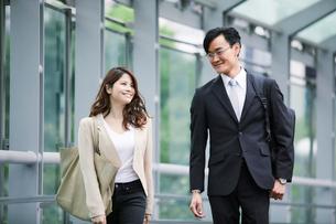 オフィス街を歩くビジネスマンとビジネスウーマンの写真素材 [FYI01802065]