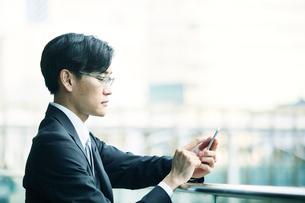 スマートフォンをもつビジネスマンの写真素材 [FYI01802067]