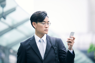 スマートフォンを持ちオフィス街を歩くビジネスマンの写真素材 [FYI01802076]