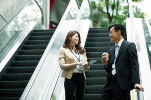 会話しながらエスカレーターに乗るビジネスマンとビジネスウーマンの写真素材 [FYI01802078]