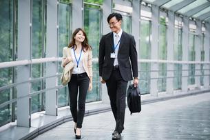 オフィス街を歩くビジネスマンとビジネスウーマンの写真素材 [FYI01802082]
