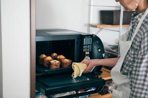 オーブンからマフィンを出す女性の写真素材 [FYI01802107]