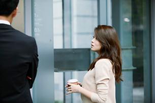 オフィスビルの前で話すビジネスマンとビジネスウーマンの写真素材 [FYI01802110]